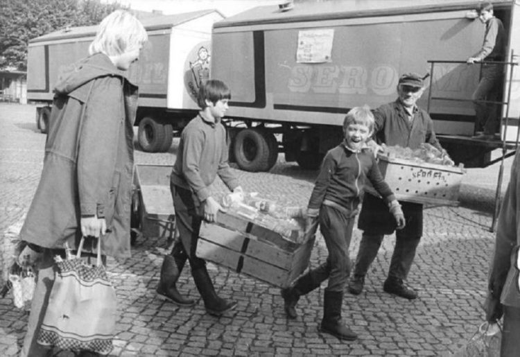 Школьники помогают взрослым в сборе стеклянной тары. ГДР, 1980-е годы.